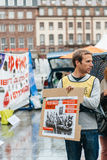 People protesting manifestation die-in against immigration policy and border management. STRASBOURG, FRANCE - APR 26 2015: Man holding placard at protest against royalty free stock images