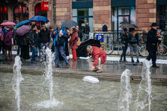 People protesting manifestation die-in against immigration policy and border management. STRASBOURG, FRANCE - APR 26 2015: Man pushing boat in fountain at royalty free stock images