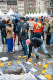 People protesting manifestation die-in against immigration policy and border management. STRASBOURG, FRANCE - APR 26 2015: Mann arranging mesages at protest royalty free stock images