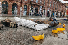People protesting manifestation die-in against immigration policy and border management. STRASBOURG, FRANCE - APR 26 2015: Puppets of dead corps and yellow paper royalty free stock photos
