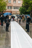 People protesting manifestation die-in against immigration policy and border management. STRASBOURG, FRANCE - APR 26 2015: People reading long list of death royalty free stock photography