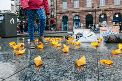 People protesting manifestation die-in against immigration policy and border management. STRASBOURG, FRANCE - APR 26 2015: Woman walking over yellow paper boats stock image
