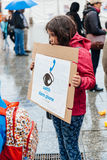 People protesting manifestation die-in against immigration policy and border management. STRASBOURG, FRANCE - APR 26 2015: Young girl holding placard at protest royalty free stock photography