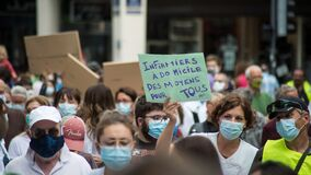 People protesting with a medical masks in the street to have more resources for hospitals and a salary increase