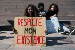 People protesting in the street against the racism with text in french : respecte mon existence , traduction in english : respect