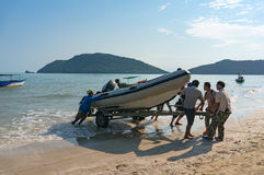 People pulling boat on shore Royalty Free Stock Image