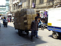 People pulling cart of boxes Royalty Free Stock Images