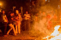 People pulling out a stick denoting the mythical figure of Prahlad from holi bonfire. Jaipur, India - 20th Mar 2019 : People pulling out a stick denoting the royalty free stock photography