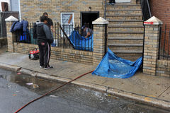 People pumping water out of building basement. BROOKLYN, NY - OCTOBER 29: People pumping water out of building basement in the Sheepsheadbay neighborhood due to Royalty Free Stock Image