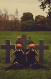 People with pumpkins on graveyard