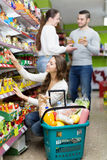 People purchasing food at supermarket. Young people purchasing a food for week in supermarket Stock Image