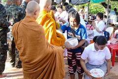 People put food offering to buddhist monk alms bowl which is the Stock Photography