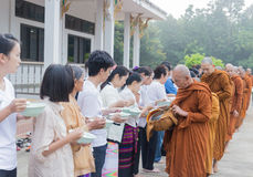 People put food offerings in a Buddhist monk's alms bowl to make Stock Images