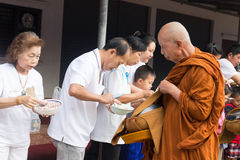 People put food offerings in a Buddhist monk's alms bowl to make Stock Photography
