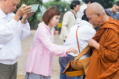 People put food offerings in a Buddhist monk's alms bowl to make Stock Image