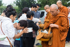 People put food offerings in a Buddhist monk's alms bowl to make Royalty Free Stock Photo