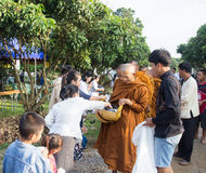 People put food offerings in a Buddhist monk's alms bowl for vir Royalty Free Stock Photos