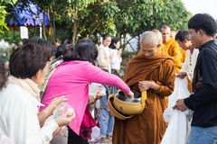 People put food offerings in a Buddhist monk's alms bowl for vir Royalty Free Stock Image