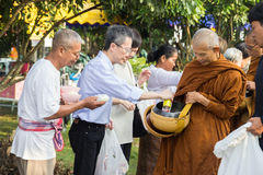 People put food offerings in a Buddhist monk's alms bowl for vir Royalty Free Stock Images