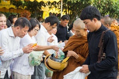 People put food offerings in a Buddhist monk's alms bowl for vir Stock Photography