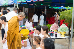 People put food offerings in a Buddhist monk's alms bowl for vir Royalty Free Stock Photography