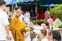 People put food offerings in a Buddhist monk's alms bowl for vir Stock Image