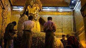 People put golden leaves on Mandalay Maha Myat Muni Buddha Image in Mahamuni Buddha Temple. Major stock video