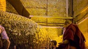 People put golden leaves on Mandalay Maha Myat Muni Buddha Image in Mahamuni Buddha Temple. It is stock footage