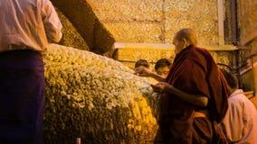 People put golden leaves on Mandalay Maha Myat Muni Buddha Image in Mahamuni Buddha Temple. It is stock video footage
