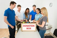 People putting cans in donation box Royalty Free Stock Photo