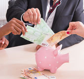 People putting cash in piggy bank - Stock Photo. Venture capital - people doing euro in a piggy bank Stock Image