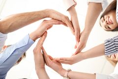 People putting their hands in circle. On light background. Unity concept royalty free stock images