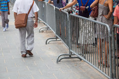 People queue behind a barrier Royalty Free Stock Photos