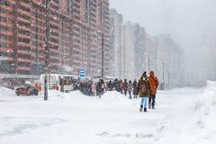 People queue for bus, heavy snow, snowstorm, rush hour, winter slippery roads, poor visibility stock photo