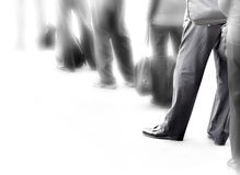 People in queue. People in dark clothes with bags waiting in queue stock photo