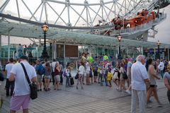 People in queue in front of London eye. LONDON, UK - AUGUST 11, 2014: People in queue in front of London eye is a giant Ferris wheel opened on 31 December 1999 stock photos
