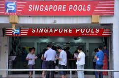 People queue outside Singapore Pools betting shop Stock Image