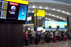 People queuing at the airport. LONDON, UK - JULY 20, 2014 : Passengers queue to check-in early morning at Heathrow Airport in London Royalty Free Stock Photo