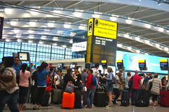 People queuing at the airport. LONDON, UK - JULY 20, 2014 : Passengers queue to check-in early morning at Heathrow Airport in London Stock Photo