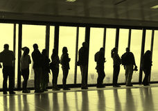 People queuing, standing next to the window in skyscraper. Silhouette of people standing by the window Stock Image