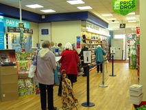 People queuing at a store checkout. People queuing at a store checkout to pay for their purchased goods. This is in the W H Smith newsagent store in Bedford stock images
