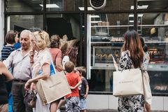 People queuing to buy bagels from a famous Beigel Shop in Brick Lane, London, UK. royalty free stock photo