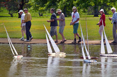 People racing remote control sailing wooden yachts Royalty Free Stock Photos