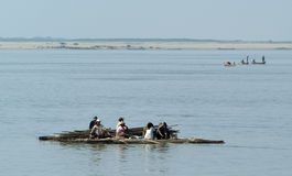 People on a raft with timber cruising on the river Ayeyarwady Royalty Free Stock Photos