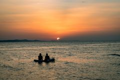 People on a raft are watching a colorful sunset in Zadar, Croatia. stock photo