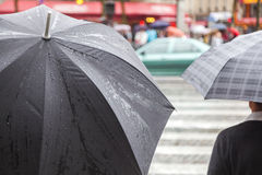 People with rain umbrellas in the rainy city. People with rain umbrellas standing at a pedestrian crossing in the rainy city Stock Images