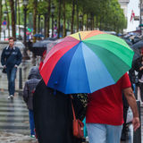 People with rain umbrellas in the rainy city. People with rain umbrellas standing at a pedestrian crossing in the rainy city of Paris at the Champs Elysees Royalty Free Stock Image