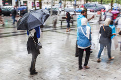 People with rain umbrellas in the rainy city. People with rain umbrellas walking in the rainy city Royalty Free Stock Image