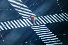 People with rainbow umbrella crossing street