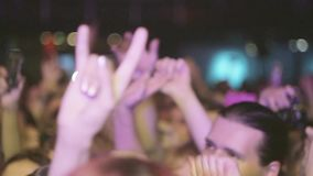 People raise hands on live rock concert in nightclub. Show two fingers. Spotlights. Illumination stock video footage